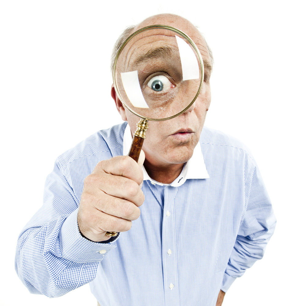 Middle-aged man looks into the camera while holding a magnifying glass up to his eye. Square shot. Isolated on white.